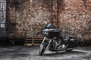 Modern black motorcycle stands against a brick wall