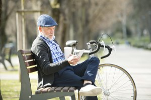 Senior man on bench with bicycle and smartphone, texting.