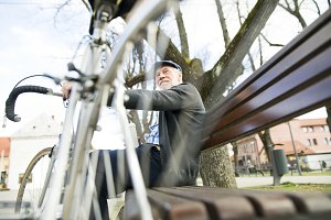 Senior man with bicycle in town, sitting on bench with coffee