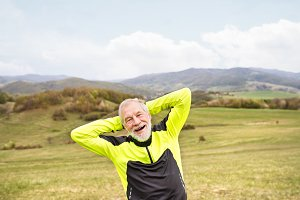 Active senior runner outside on green hills doing stretching.