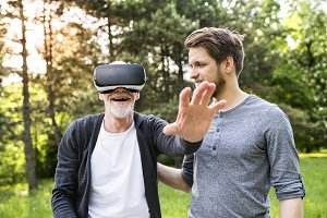 Young man and his senior father with VR glasses outdoors.
