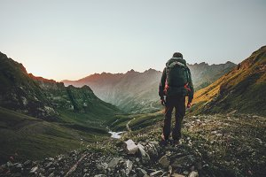 Man hiking at sunset mountains