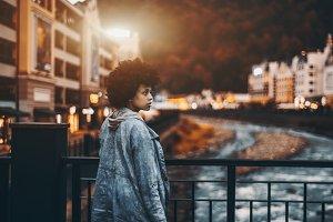 Black girl in evening city on bridge