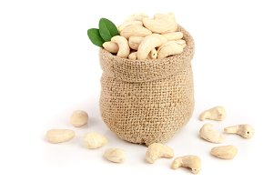 cashew nuts with leaf in bag isolated on white background