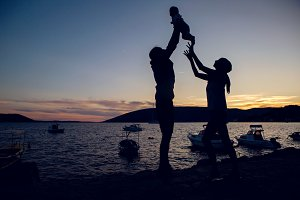 parents throw baby sunset