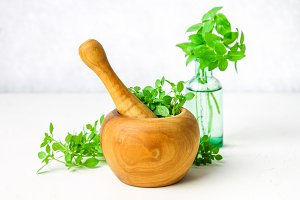Green lemon basil in a wooden mortar on a light background. Behind the basil in the bottle.