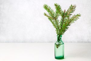 Christmas decorations on the table, spruce branch in the bottle