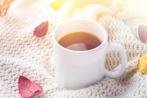 Mug of hot coffee in autumn setting on a wooden table with a knitted scarf, sweater. Comfort, warmth, cozy.