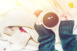 Mug of hot coffee in a woman's hand in a sweater in the autumn setting on a wooden table with a knitted scarf, sweater. Comfort, warmth, cozy.