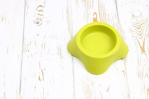 Yellow-green empty plastic bowl for pets on a white wooden floor.