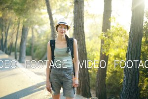 Portrait of Attractive tourist girl smiling and looking into camera while walking and hiking beautiful forest