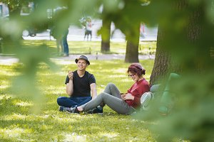 Young couple tourists with backpacks have rest in the park