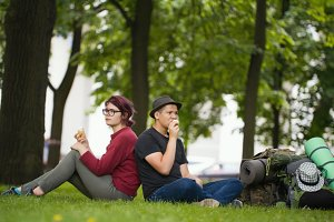 Young couple tourists with backpacks are eating the icecream in the park
