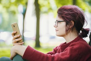 Portrait of a young teenager girl with smartphone in a summer city park