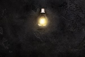 Burning light bulb in darkness