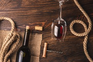 Glass with wine, bottle, corkscrew and burlap, top view