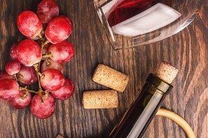 Glass with wine, bottles and bunch of grapes, wooden background