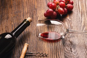 Glass with wine, corkscrew, bottle and grape