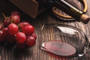 Glass with wine, a bottle and bunch of ripe grape, wooden background