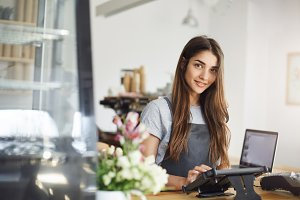 Coffee shop owner using a tablet looking at camera smiling, ready for her first customer