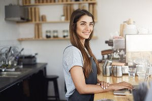 Young woman barista at her workplace looking happy smiling working on a laptop