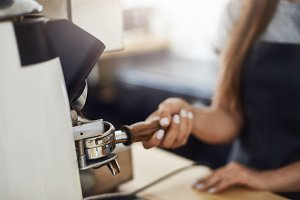 Close up of barista using coffee grinder to fill a portafilter