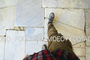 Top view POV of man in sneakers walking historical ancient sidewalk