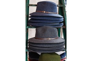 Close-up of stack of fashion female wool hats gray and blue colors.
