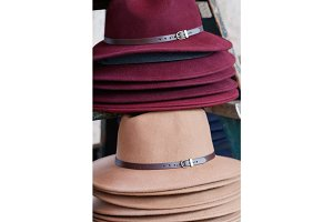 Close-up of stack of fashion female wool hats purple and beige colors.