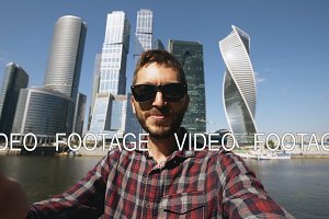 Happy tourist man having online video chat using his smartphone camera near international business center in Moscow