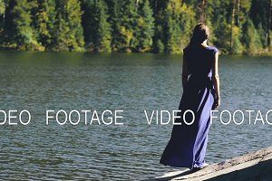 Slowmotion of Beautiful young woman in long dress standing on shore near lake