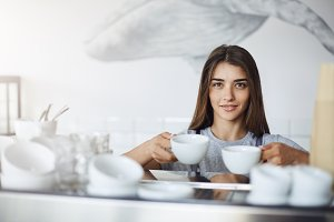 Female barista holding coffee and tea cups for cappuccino ready to put them onto an espresso machine to warm them up