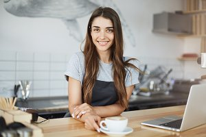 Small coffee shop owner happy to run her business looking at camera smiling and drinking coffee.