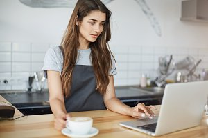 Female barista running her coffee business having a small break surfing web and social media on a laptop.