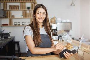 Female coffee shop employee using a credit card reader to bill the customer looking happy smiling at camera.