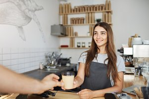 Young lady barista serving coffee to go to her first customer today looking happy.