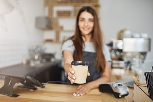 Close up of barista serving coffee to go cup to a customer.