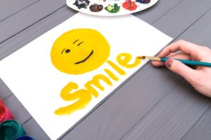 Hand draws smile on sheet