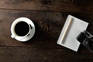 Top view of black coffee and blank notebook on wooden