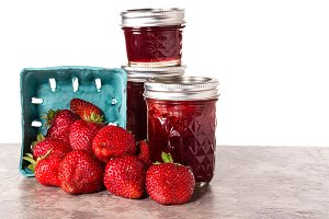 Strawberries and jars of jam