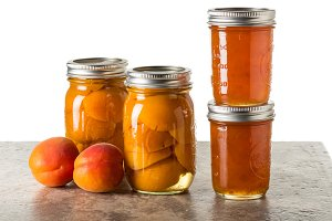 Ripe apricots with jars of preserves