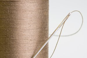 Spool of brown thread with needle