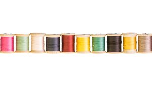 Row of thread spools on white