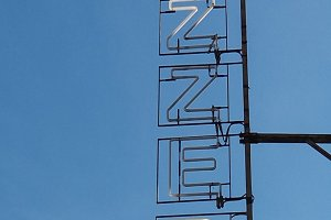 Pizzeria sign over blue sky