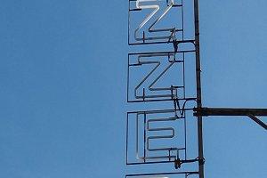 Pizzeria sign over blue sky