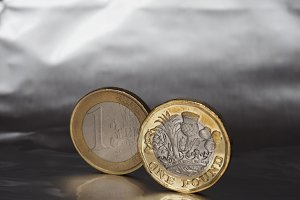 1 pound and 1 euro coin over metal background