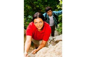 Young Couple Climbing Up A Mountain