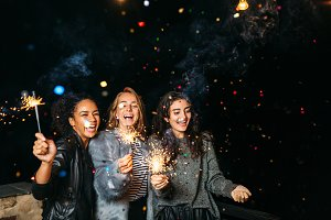 Three happy women with sparklers