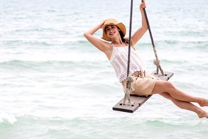 girl stands on a swing on the beach of Thailand