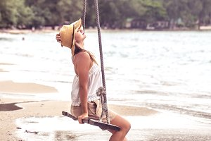 girl on the swing on the beach of Thailand